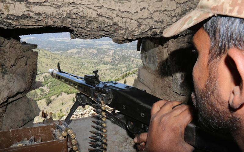A Pakistani soldier keeps vigil from a post on top of a mountain in the former Taliban militants stronghold border area in Shawal valley