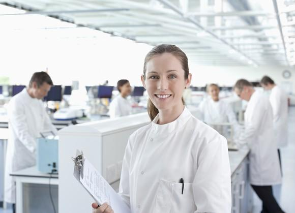 Smiling scientist with a clipboard.