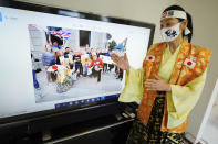 """Olympic fan Kyoko Ishikawa shows an image on a TV screen showing her at London Olympics with local people Saturday, April 10, 2021, in Tokyo.Ishikawa, president of an IT company, has attended every Summer Olympics since Barcelona in 1992, becoming famous as an unofficial """"International Olympic Cheerleader."""" She relishes joining in with fans from everywhere to cheer for their athletes. (AP Photo/Eugene Hoshiko)"""