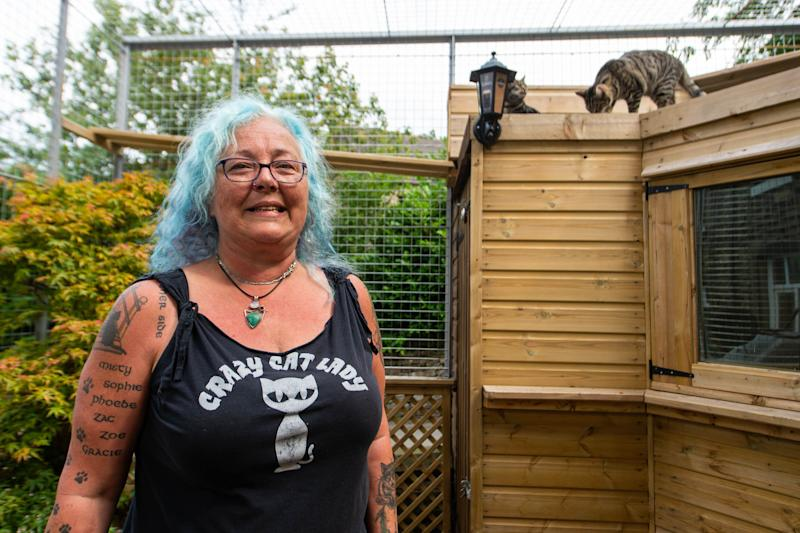 Sue Haworth in the cage for her cats at her home (Picture: SWNS)