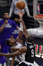 Sacramento Kings guard De'Aaron Fox, left, shoots as Los Angeles Clippers center Serge Ibaka defends during the first half of an NBA basketball game Sunday, Feb. 7, 2021, in Los Angeles. (AP Photo/Mark J. Terrill)