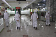 """FILE - In this Dec. 28, 2020, file photo, staff of the Pyongyang Department Store No. 1 disinfect the store to help curb the spread of the coronavirus before it opens in Pyongyang, North Korea. A North Korean website says the country will not participate in the Tokyo Olympics because of the coronavirus pandemic. The Sports in DPR Korea website said Tuesday, April 6, 2021 the decision was made during a national Olympic Committee meeting on March 25 where members prioritized protecting athletes from the """"world public health crisis caused by COVID-19."""" (AP Photo/Jon Chol Jin, File)"""