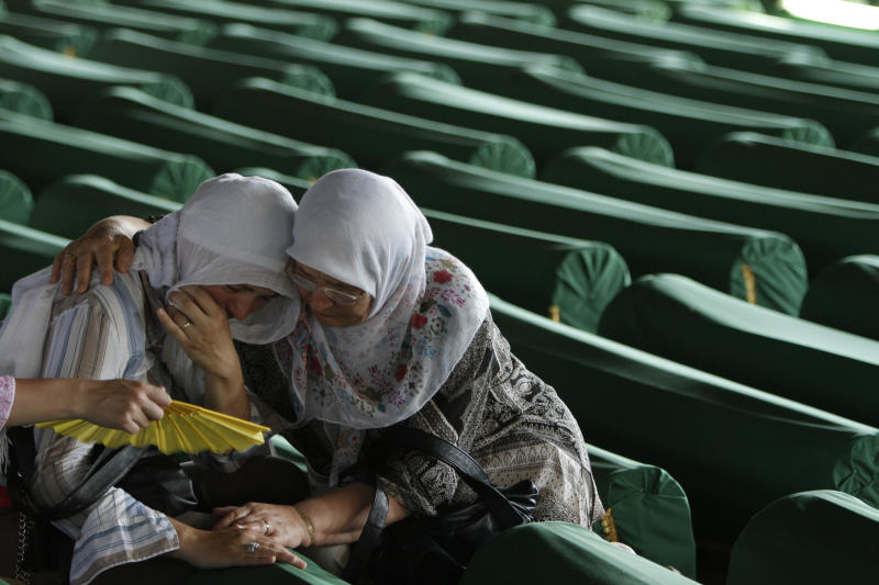 Bosnian Muslim women cry as they touch the coffin of a relative, among 520 newly identified Srebrenica victims, at the Potocari memorial cemetery near Srebrenica, some 160 kilometers east of Sarajevo, Bosnia and Herzegovina, Monday, July 9, 2012. The 520 victims will be buried at a memorial center near Srebrenica on the 17th anniversary of the massacre of 8,000 men and boys, defined by the International Court of Justice as genocide. (AP Photo/Amel Emric)