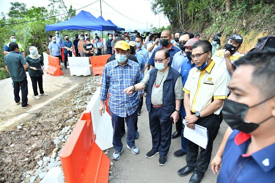 Sabah Chief Minister Datuk Seri Hajiji Noor (left) observes repair work on a damaged stretch of road between Penampang and Tambunan January 26, 2021. — Picture by Julia Chan