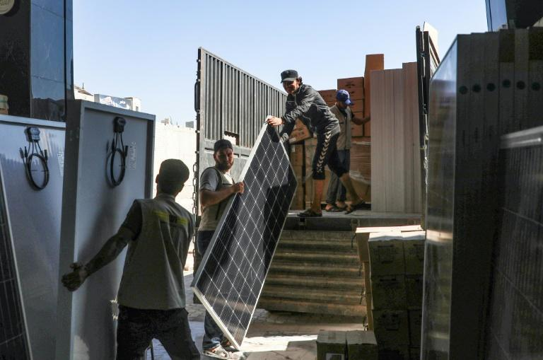 Workers unload solar panels from a truck in Dana in Syria, which provide power in areas without state-provided electricity