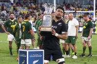 New Zealand's Ardie Savea embraces the Freedom Cup following the Rugby Championship test match between the Springboks and the All Blacks in Townsville, Australia, Saturday, Sept. 25, 2021. (AP Photo/Tertius Pickard)