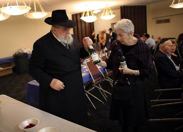 MIAMI BEACH, FL - MARCH 25: Rabbi Efraim Katz gives wine to Pauline Kopelman to be placed on a table as he leads a community Passover Seder at Beth Israel synagogue on March 25, 2013 in Miami Beach, Florida. The community Passover Seder that served around 150 people has been held for the past 30 years and is welcome to anyone in the community that wants to commemorate the emancipation of the Israelites from slavery in ancient Egypt. (Photo by Joe Raedle/Getty Images)