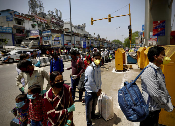 Indians line up to board trains outside New Delhi railway station in New Delhi, India, Tuesday, May 12, 2020. India is reopening some of its colossal rail network as the country looks at easing its nearly seven-week strict lockdown amid an increase in coronavirus infections. (AP Photo/Manish Swarup)