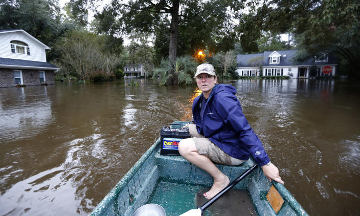 <p>Jeanni Adame rides in her boat as she checks on neighbors seeing if they want to evacuate in the Ashborough subdivision near Summerville, S.C., after many of their neighbors left, Monday, Oct. 5, 2015. South Carolina is still struggling with flood waters due to a slow moving storm system. (AP Photo/Mic Smith) </p>
