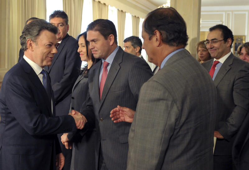 In this photo released by Colombia's Presidential Office, President Juan Manuel Santos, left, shakes hands with his Defense Minister Juan Carlos Pinzon as other cabinet ministers surround him after he announced the signing of a preliminary agreement to launch peace talks with the Revolutionary Armed Forces of Colombia, or FARC, a nationally televised speech from the presidential palace in Bogota, Tuesday, Sept. 4, 2011. Santos said the talks would begin in early October in Oslo, Norway, and would continue in Havana, Cuba. (AP Photo/Javier Casella, Colombia's Presidential Office)