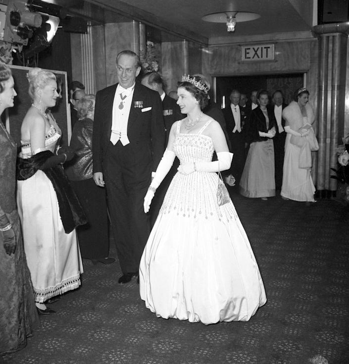 """<p>While attending the premiere of <em>Lawrence of Arabia </em>in 1962, the Queen wore a taffeta and crystal ball gown designed by Norman Hartnell. The dress would make a public appearance almost 60 years later on the Queen's granddaughter, Princess Beatrice. The young royal <a href=""""https://www.harpersbazaar.com/celebrity/latest/a34403448/princess-beatrice-wedding-gown-grandmother-queen/"""" rel=""""nofollow noopener"""" target=""""_blank"""" data-ylk=""""slk:borrowed and altered her grandmother's gown"""" class=""""link rapid-noclick-resp"""">borrowed and altered her grandmother's gown</a> for her wedding day in 2020. </p>"""
