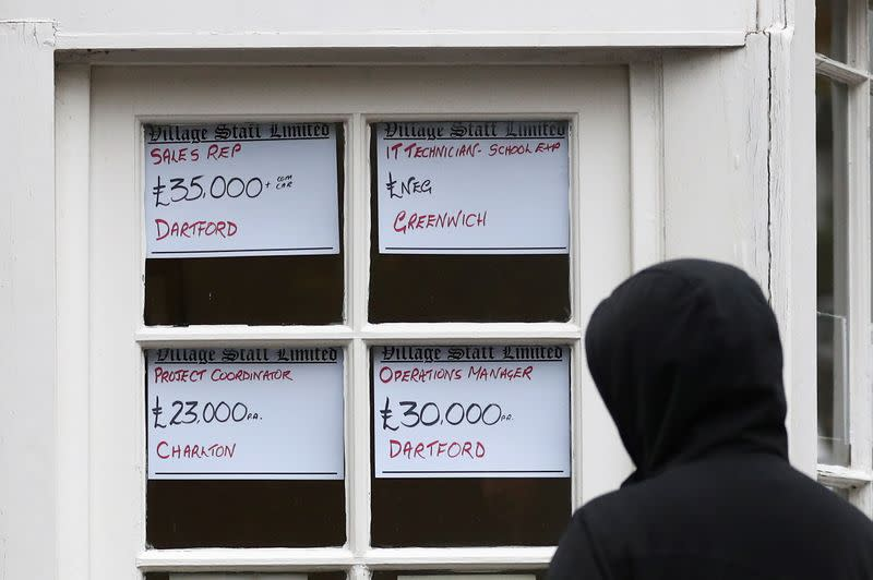 FILE PHOTO: A person looks at adverts in the window of a job agency in London