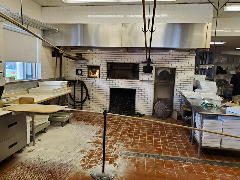 Every step of production from rolling out the dough on a floured surface to cooking in the coal ovens to slicing and boxing, is done in full view of customers. Because the ovens are so hot, the require custom extra long handled pizza peels, hanging from hooks.