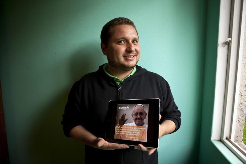 In this July 15, 2013 photo, Jorge Cavazos poses for a photo holding his tablet showing a photo of Pope Francis in his dorm at the Pontifical University of Mexico seminary in Mexico City. Jorge Cavazos made the decision to become a priest at 21. Thirteen years later, he hasn't changed his mind despite the pedophilia and cover-up scandals at the Catholic Church and a very long process he hasn't yet completed. Cavazos at age 8 was an altar boy and at 21 entered the seminary. (AP Photo/Ivan Pierre Aguirre)