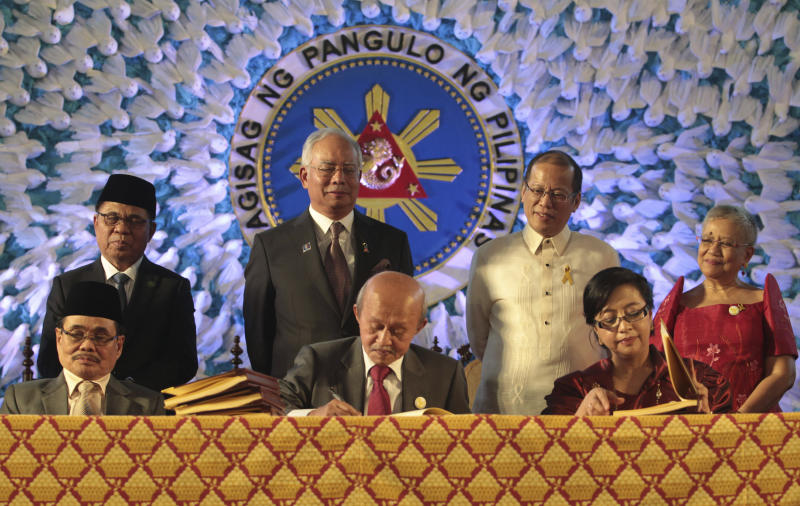 In this handout photo released by the Malacanang Photo Bureau, President Benigno S. Aquino III, back row secon from right, Malaysian Prime Minister Najib Razak, back row second from left, Moro Islamic Liberation Front (MILF) Chairman, Al Haj Murad Ebrahim, back row left, and Secretary Teresita Quintos-Deles, seated left, Presidential Adviser on the Peace Process, back row right, witness the signing of the Comprehensive Agreement on the Bangsamoro (CAB) by MILF chief negotiator Mohagher Iqbal, Datu Tengku Gnafar, seated center, and Miriam Coronel Ferrer, seated right, of the Philippine government in a ceremony at the Malacanang Presidential Palace in Manila, Philippines on Thursday March 27, 2014. The Philippine government signed a peace accord with the country's largest Muslim rebel group on Thursday, the culmination of years of negotiations and a significant political achievement for President Aquino.(AP Photo/Malacanang Photo Bureau, Benhur Arcayan)