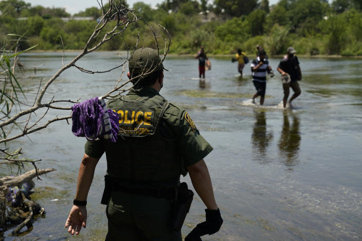 FILE - In this June 15, 2021, file photo, a Border Patrol agent watches as a group of migrants walk across the Rio Grande on their way to turning themselves in upon crossing the U.S.-Mexico border in Del Rio, Texas. A Justice Department attorney says the U.S. Centers for Disease Control and Prevention will issue an order this week about treatment of children under a public health order that has prevented migrants from seeking asylum at U.S. borders. (AP Photo/Eric Gay, File)