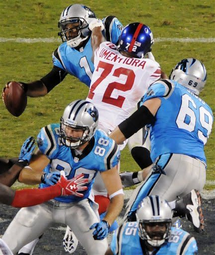 Carolina Panthers quarterback Cam Newton (1) is sacked by New York Giants defensive end Osi Umenyiora (72) during the second quarter of an NFL football game in Charlotte, N.C., Thursday, Sept. 20, 2012. (AP Photo/Mike McCarn)