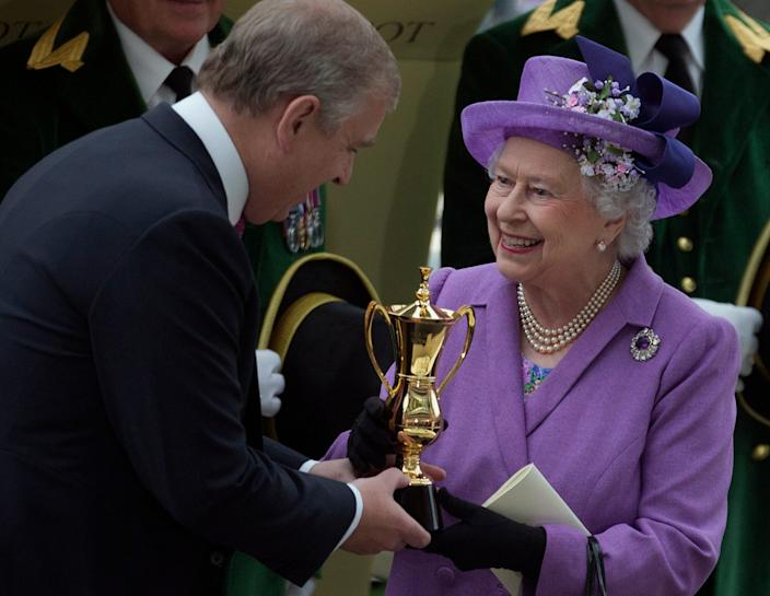Prince Andrew, the Duke of York, presents his mother, Queen Elizabeth II, with a trophy after her horse Estimate won the Gold Cup at Royal Ascot in June 2013.