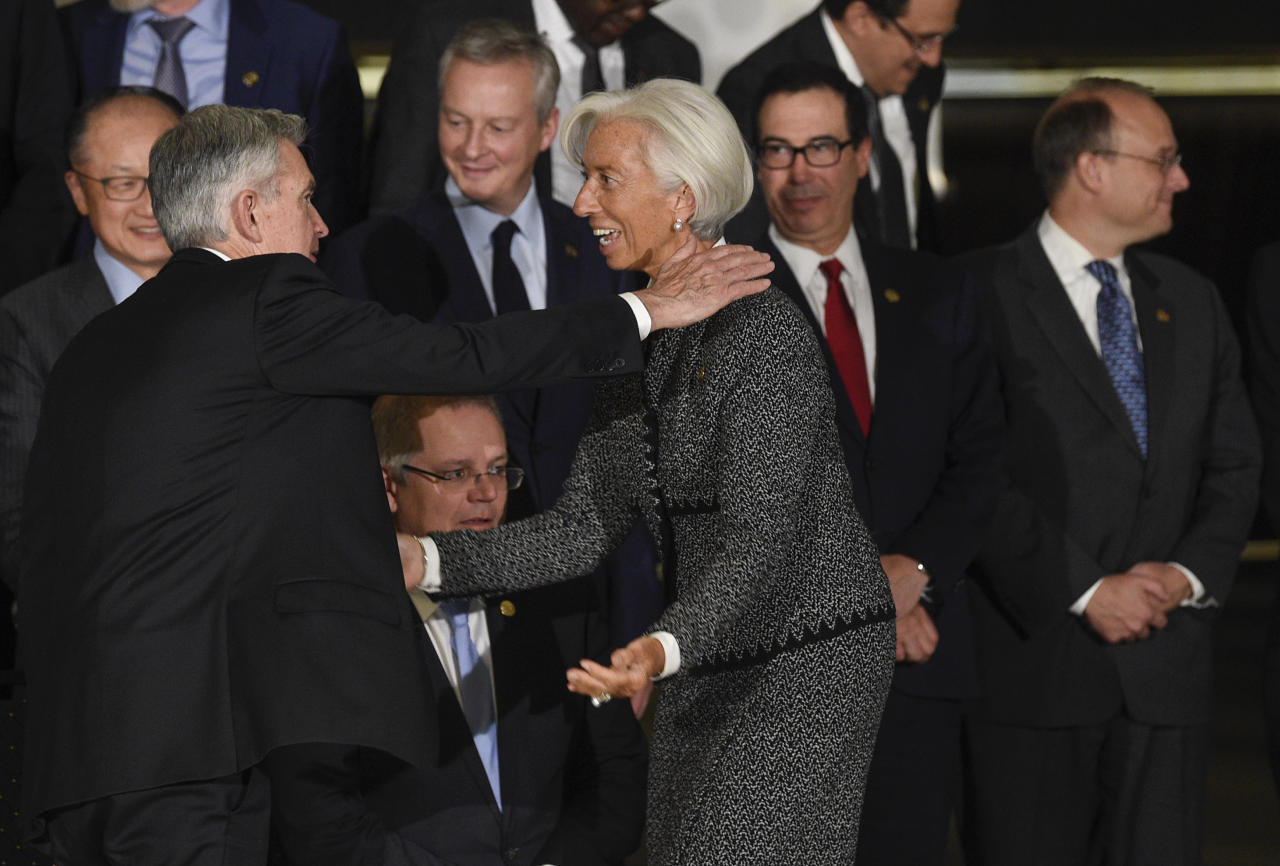 International Monetary Fund Director Christine Lagarde reaches out to embrace Jerome Powell, chairman of the Federal Reserve, as they gather for a group picture at the G20 Meeting of Finance Ministers in Buenos Aires, Argentina, Saturday, July 21, 2018. (AP Photo/Gustavo Garello)