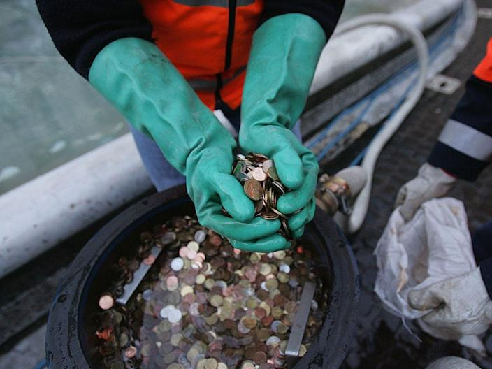 <br>A man holding coins collected from the Trevi Fountain in Rome.