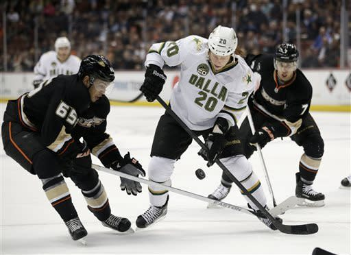 Dallas Stars' Cody Eakin, center, fights for the puck with Anaheim Ducks' Emerson Etem, left, and Andrew Cogliano during the first period of an NHL hockey game in Anaheim, Calif., Wednesday, April 3, 2013. (AP Photo/Jae C. Hong)