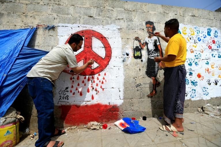 Yemeni artists paint a pro-peace graffiti on a wall in the capital Sanaa on August 16, 2018 as they call for peace and tolerance and rejecting the ongoing conflict in the Arab world's most impoverished country