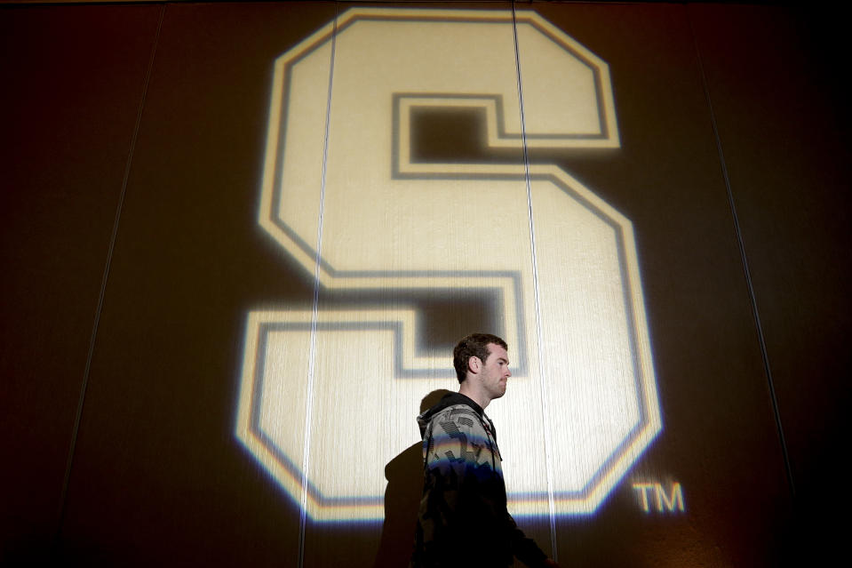 Stanford quarterback Kevin Hogan walks past the school logo projected on the wall during a news conference on Friday, Dec. 27, 2013, in Los Angeles. Stanford is scheduled to play Michigan State in the Rose Bowl NCAA college football game in Pasadena, Calif., on New Year's Day. (AP Photo/Jae C. Hong)