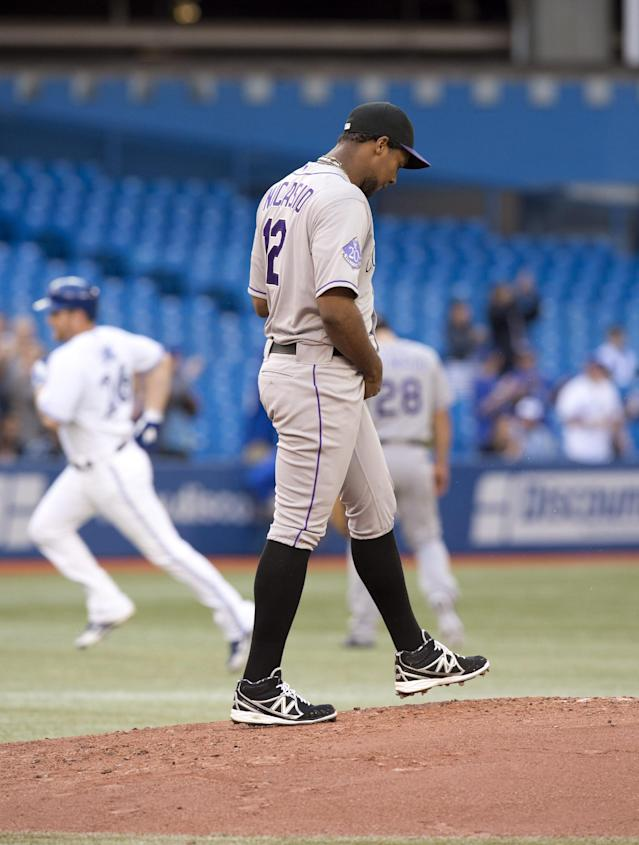 Toronto Blue Jays' Adam Lind rounds the bases with three-run hom run as Colorado Rockies starting pitcher Juan Nicasio kicks the mound during first inning of a baseball game in Toronto on Wednesday, June 19, 2013. (AP Photo/The Canadian Press, Frank Gunn)