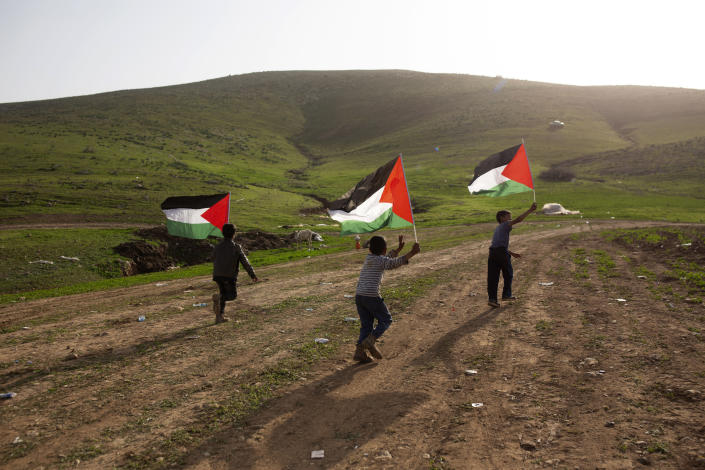 Palestinian Bedouin boys play with Palestinian flags after Israeli troops demolished tents and other structures of the Khirbet Humsu hamlet in the Jordan Valley in the West Bank, Wednesday, Feb. 3, 2021. A battle of wills is underway in the occupied West Bank, where Israel has demolished the herding community of Khirbet Humsu three times in as many months, displacing dozens of Palestinians. Each time they have returned and tried to rebuild, saying they have nowhere else to go. (AP Photo/Maya Alleruzzo)