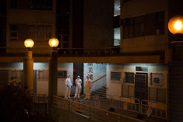 PHOTO: Officials wearing protective gear stand guard outside an entrance to the Hong Mei House residential building at Cheung Hong Estate in the Tsing Yi district, Hong Kong, China, on Feb. 11, 2020. (Billy H.c. Kwok/Getty Images)
