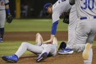 Los Angeles Dodgers relief pitcher Dustin May, left, is comforted by Dodgers' David Freese, second from right, as manager Dave Roberts (30) runs on the field during the fourth inning of a baseball game, after May was hit by a batted ball from Arizona Diamondbacks' Jake Lamb Sunday, Sept. 1, 2019, in Phoenix. (AP Photo/Ross D. Franklin)