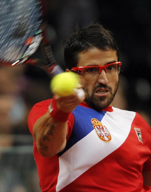 Janko Tipsarevic of Serbia returns a ball to Vasek Pospisil of Canada during their Davis Cup semifinal tennis match in Belgrade, Serbia, Sunday, Sept. 15, 2013. (AP Photo/Darko Vojinovic)