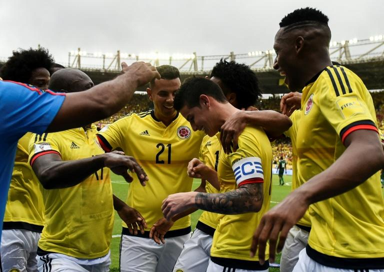 Colombia's midfielder James Rodriguez (2nd R) is congratulated by teammates after scoring a goal against Bolivia on penalty during their 2018 FIFA World Cup qualifier match, in Barranquilla, on March 23, 2017