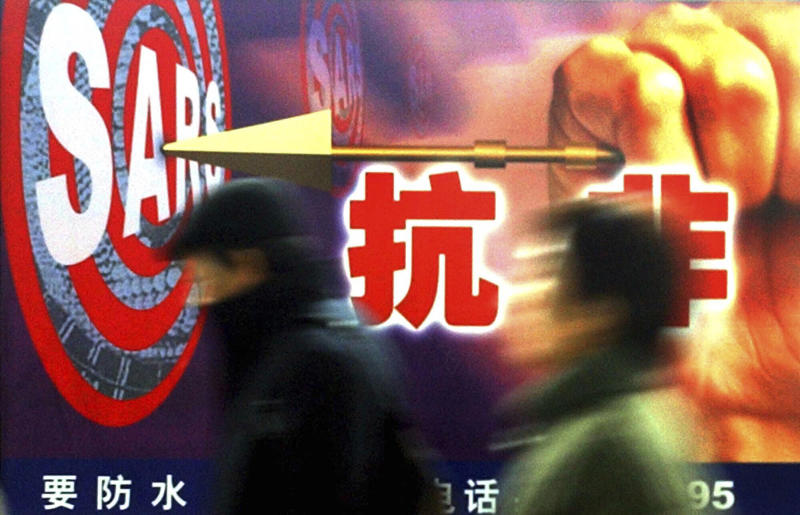 "FILE - In this Dec. 18, 2003, file photo, people walk past a local government 's anti-SARS advertisement in Shanghai, China. Nearly two decades after the disastrously-handled SARS epidemic, China's more-open response to a new virus signals its growing confidence and a greater awareness of the pitfalls of censorship, even while the government is as authoritarian as ever. Chinese characters on the advertisement says ""Anti-SARS."" (AP Photo/Eugene Hoshiko)"