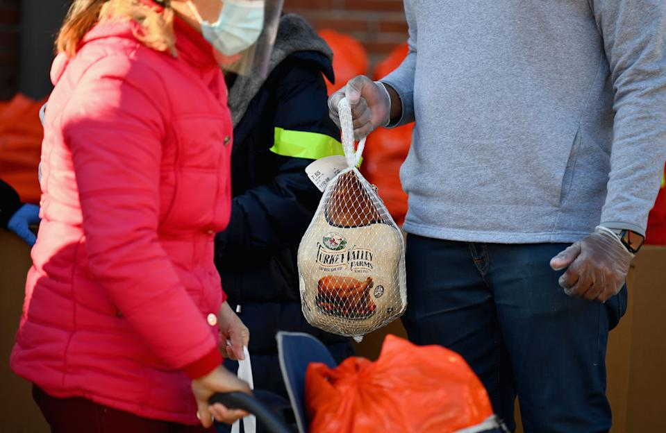 Turkeys are given to residents at a food distribution event ahead of the Thanksgiving holiday on November 20, 2020, in the Brooklyn borough of New York City. (Photo by ANGELA WEISS/AFP via Getty Images)