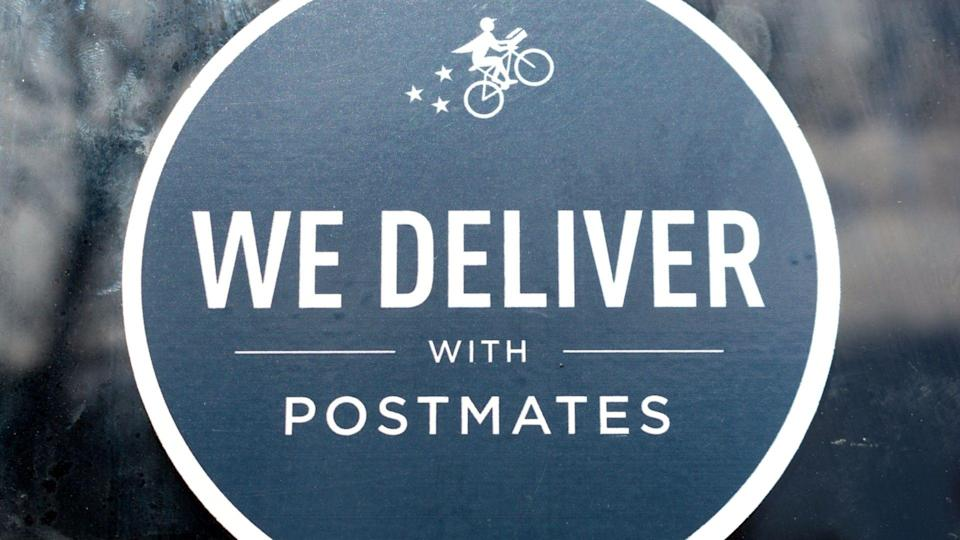 Close up. Postmates black sticker decal advertising delivery service available through Postmates goods delivery service - San Jose, California, USA - 2020