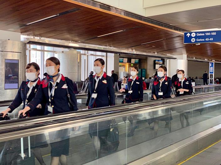 Japan Airline crew are seen at Los Angeles International Airport wearing masks to prevent coronavirus infection: Getty