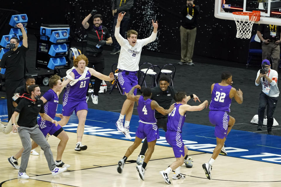 Abilene Christian players celebrate their 53-52 upset win over Texas in a college basketball game in the first round of the NCAA tournament at Lucas Oil Stadium in Indianapolis Sunday, March 21, 2021. (AP Photo/Mark Humphrey)