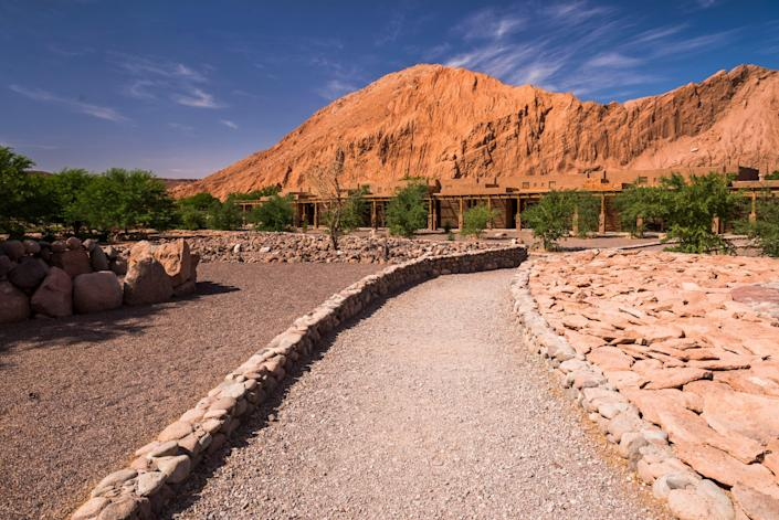 The Hotel Alto Atacama Desert Lodge and Spa in Chile blends into the desert rocks above.