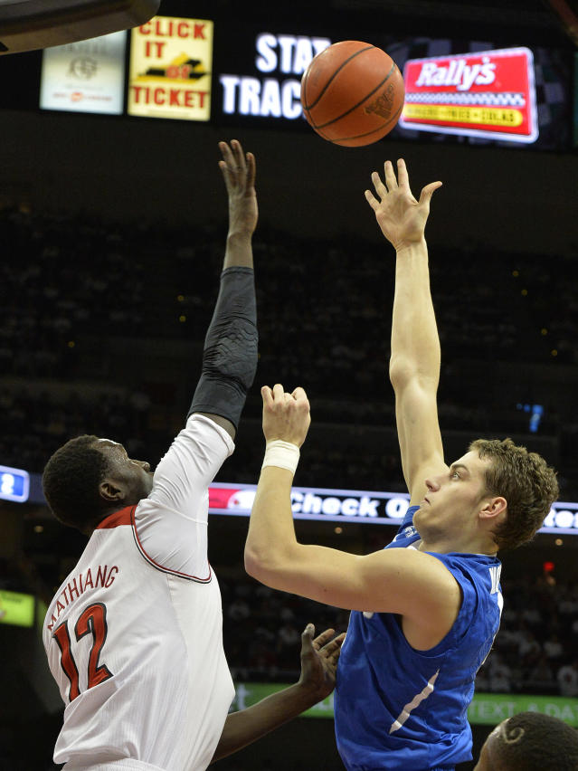 Memphis' Austin Nichols, right, shoots over the defense of Louisville's Mangok Mathiang during the first half of an NCAA college basketball game on Thursday Jan. 9, 2014, in Louisville, Ky. (AP Photo/Timothy D. Easley)
