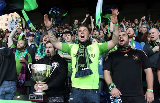 Seattle Sounders fan Darin Schneider, center, shouts while Glenn White holds the Cascadia Cup before the start of an MLS soccer game between the Sounders and the Portland Timbers, Sunday, June 24, 2012, in Portland, Ore. (AP Photo/Rick Bowmer)