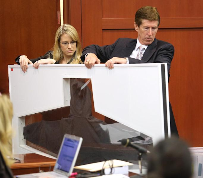 Defense counsel Mark O'Mara and an assistant carry Trayvon Martin's hooded sweatshirt in the George Zimmerman trial in Seminole Circuit Court, in Sanford, Fla., Tuesday, July 9, 2013. Zimmerman is charged with second-degree murder in the fatal shooting of Trayvon Martin, an unarmed teen, in 2012. (AP Photo/Orlando Sentinel, Joe Burbank, Pool)