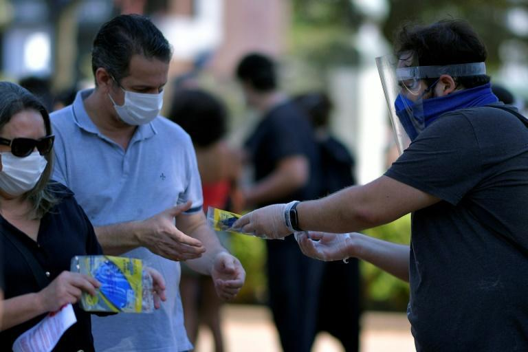A man hands out medical masks at a rally against Brazil's President Jair Bolsonaro in Belo Horizonte