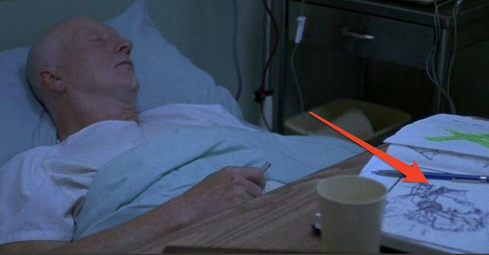 """John Kramer laying in hospital bed with his sketchbook on table in front of him in """"Saw."""""""
