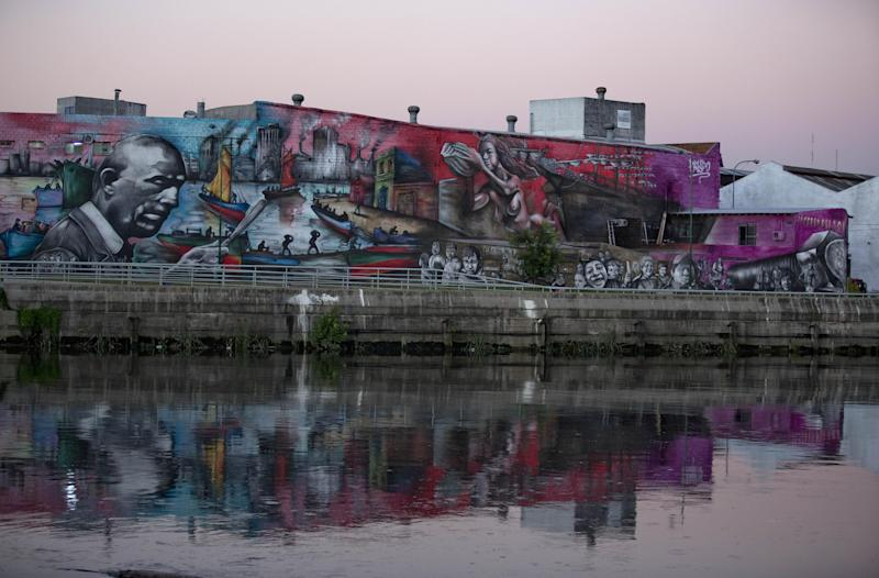 A mural honoring the Argentine painter Benito Quinquela Martin by artist Alfredo Segatori is reflected in the waters of the Riachuelo river in Barracas neighborhood, in Buenos Aires, Argentina, Tuesday, Dec. 3, 2013. A report by the environmental activist groups Blacksmith Institute and Green Cross of Switzerland ranked the Riachuelo as the eighth most polluted place in the world. The study says makers of chemical products are responsible for more than a third of the river's contamination, and adds that sample testing indicated 80 percent of water taken from wells near the river is not safe to be consumed. (AP Photo/Natacha Pisarenko)