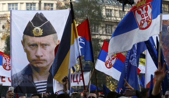 In this Saturday, Nov. 15, 2014 file photo, a supporter of Serbian ultranationalist leader Vojislav Seselj holds a picture of Russian President Vladimir Putin during a protest In Belgrade, Serbia. Vladimir Putin has accused the U.S. and the West of destabilizing the Balkans with NATO expansion policies as Serbia prepares a hero's welcome for the Russian president. (AP Photo/Darko Vojinovic, File)