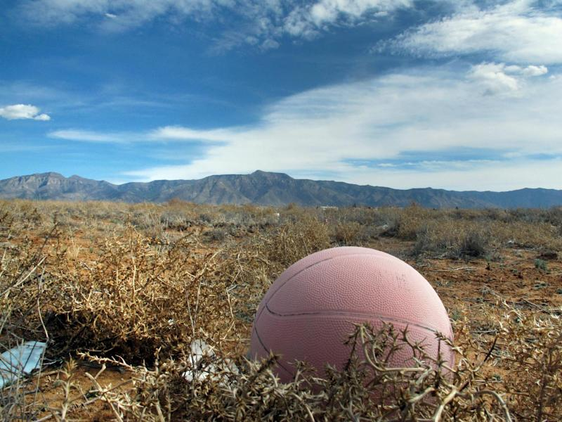 An old basketball in an abandon lot south of Albuquerque is shown where authorities say the body of a 12-year-old boy was discovered, Wednesday, Feb. 19, 2014, in Meadow Lake, N.M. Valencia County Sheriff Louis Burkhard said Alex Madrid of Albuquerque was found in the field Tuesday after his parents reported him missing. The 15-year-old taken into custody in connection to Madrid's death has been identified as Brandon Villalobos. (AP Photo/Russell Contreras)