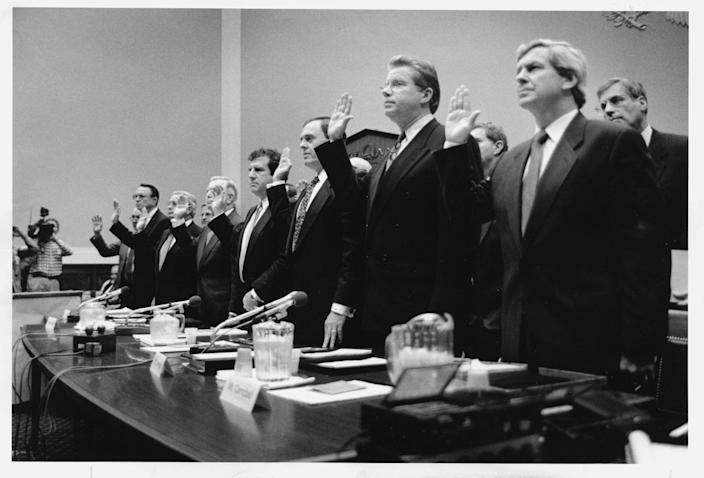 Tobacco executives from Research American Tobacco, American Tobacco, Brown & Williamson, Liggett Group, Lorillard Tobacco, U.S. Tobacco, RJR Tobacco, and Phillip Morris USA, are sworn in to testify before Capitol Hill hearing in April 1994. (Ray Lustig/The Washington Post via Getty Images)
