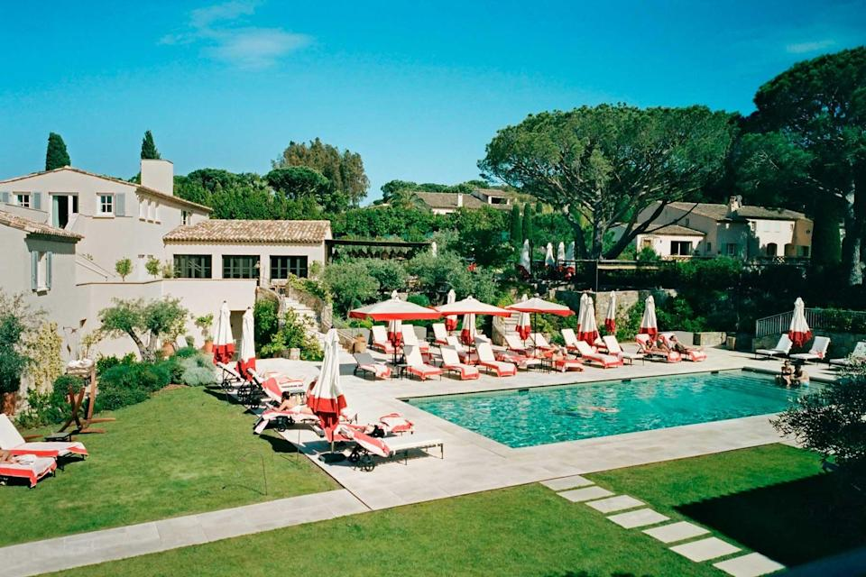 A hotel pool in St Tropez surrounded by red and white deck chairs