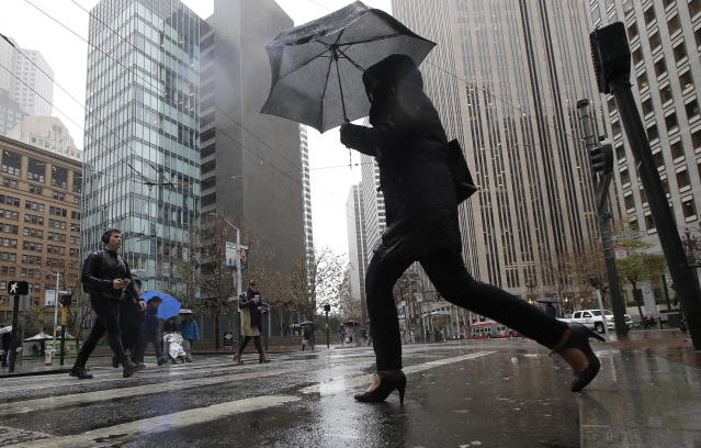 A woman carries an umbrella while crossing a street in San Francisco, Tuesday, Jan. 15, 2019. The first in a series of Pacific storms brought rain to much of the state and snow in the mountains. (AP Photo/Jeff Chiu)